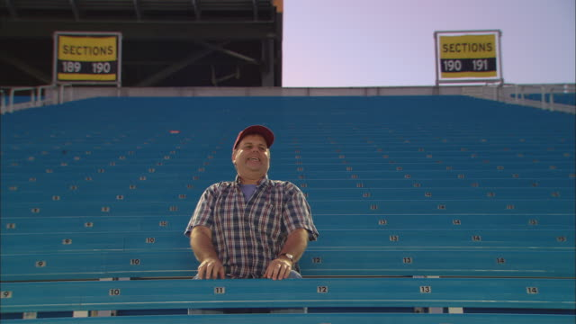 la ws excited man stretching and sitting down in empty bleachers / homestead, fl, usa - miami dade county stock videos and b-roll footage