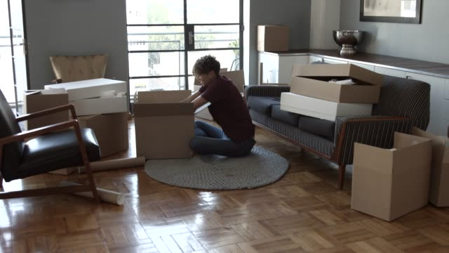 excited man unpacking cardboard box at new home - packing stock videos & royalty-free footage