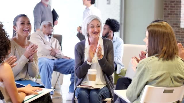 excited mature woman shares good news with support group - group therapy stock videos & royalty-free footage