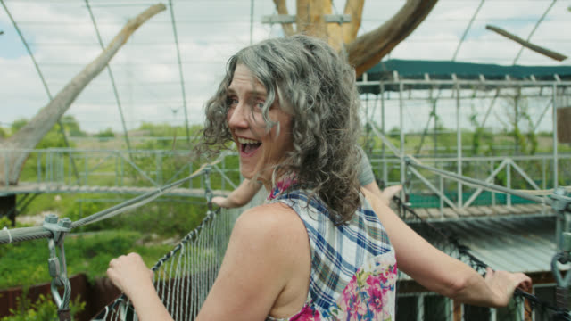 vidéos et rushes de pov slo mo. excited mom running across ropes course drawbridge with daughters looks back and laughs. - femme mure