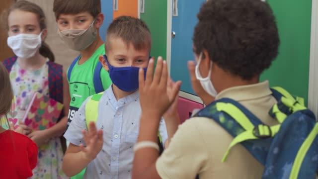 stockvideo's en b-roll-footage met opgewekte multiraciale groep schoolkinderen die van hun eerste dag op school tijdens covid-19 pandemie genieten terwijl het spelen klappen spel - opluchting