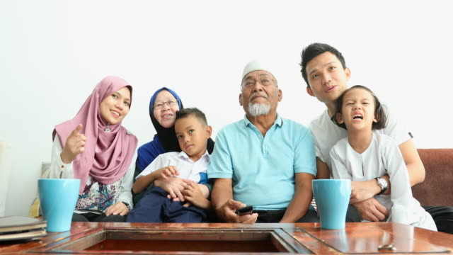 excited muslim three generation asian family watching tv together - cultura malesiana video stock e b–roll