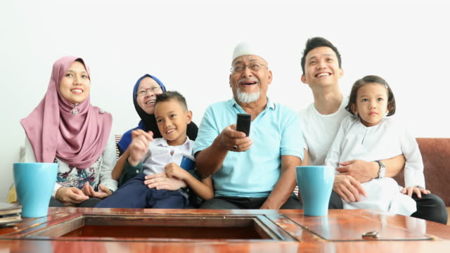 excited muslim three generation asian family watching tv together - headscarf stock videos & royalty-free footage