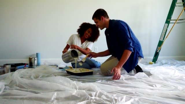 vídeos de stock e filmes b-roll de excited new homeowners prepare to paint inside their new home - pano de protecção