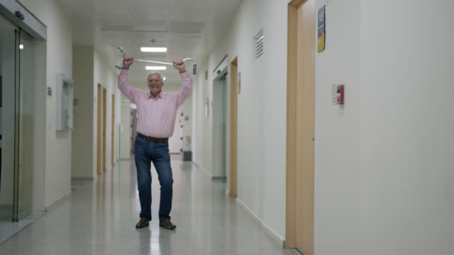 excited senior man leaving the hospital dancing and looking very happy - leaving hospital stock videos & royalty-free footage