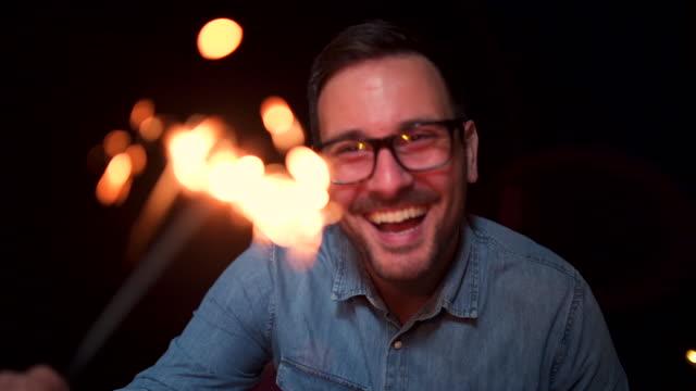 vídeos de stock e filmes b-roll de excited smiling man celebrating new year with sprinkler - ano novo