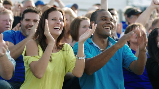 excited spectators at sporting event clap and cheer. - sports race stock videos & royalty-free footage