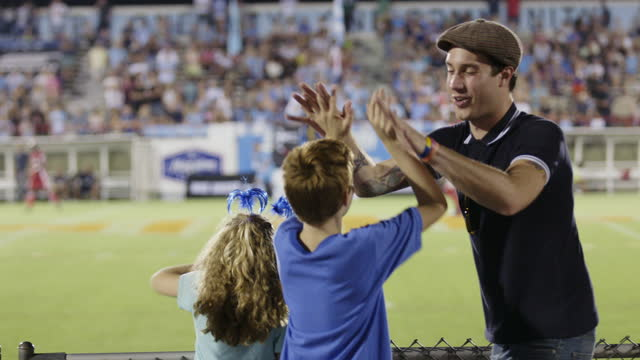 WS. Excited sports fan high fives little boy from stadium bleachers at professional soccer match.