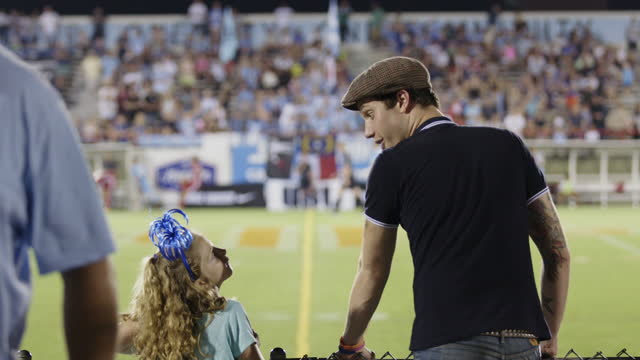 WS. Excited sports fan makes eye contact with little girl on sideline of professional soccer game.