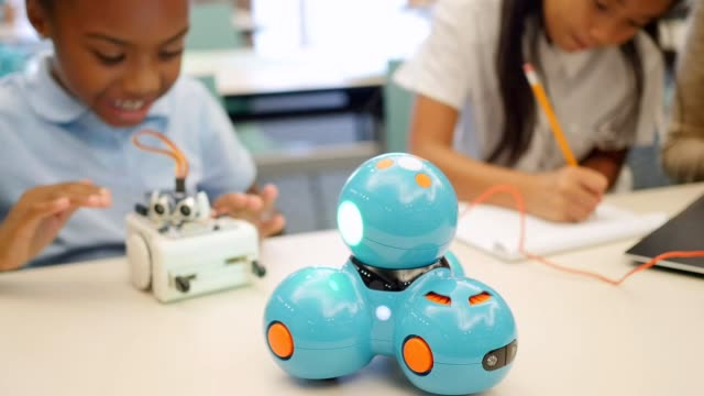 Excited STEM elementary school students test robots in technology class
