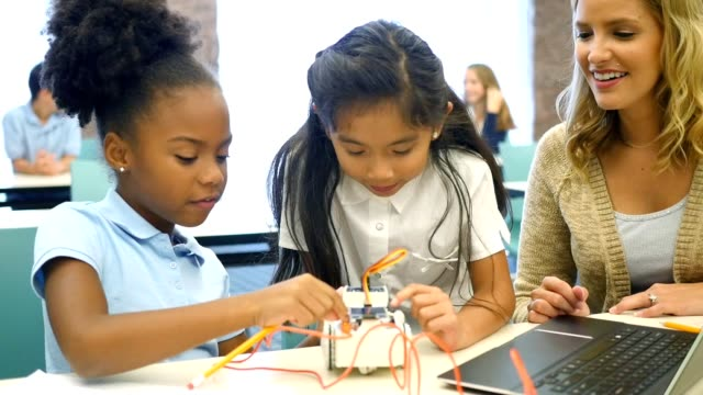 Excited STEM school girls build robot in technology class