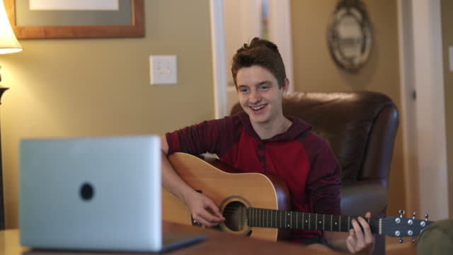 excited teenager learning to play the guitar at home via video call - sweatshirt stock videos & royalty-free footage