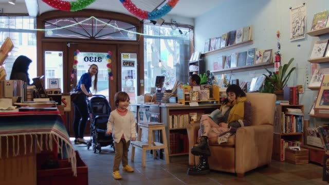excited toddler arriving in bookstore with his mom - bookstore stock videos & royalty-free footage