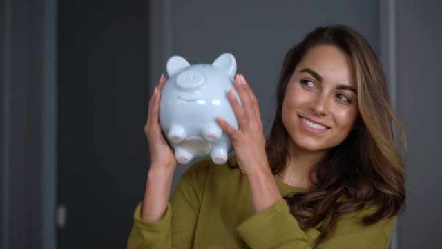 excited woman at home shaking her piggy bank smiling - piggy bank stock videos & royalty-free footage
