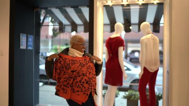 vídeos y material grabado en eventos de stock de mujer emocionada bailando y probando ropa en una tienda - 40 seconds or greater