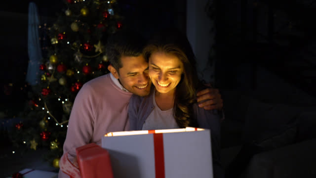 excited woman opening her christmas present from partner while he kisses her on the cheek - christmas gift stock videos & royalty-free footage