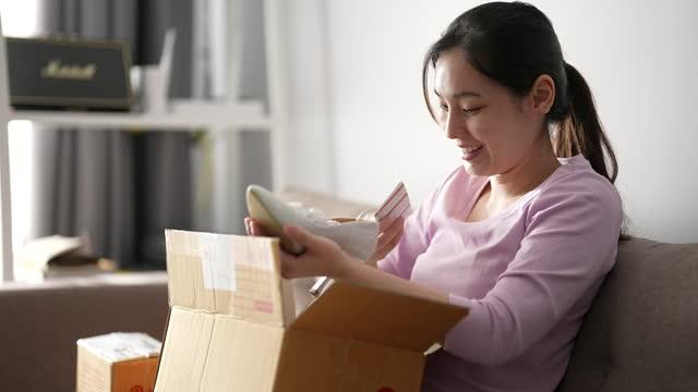 興奮した若いアジアの女性の顧客が自宅で小包箱を開ける - 受ける点の映像素材/bロール