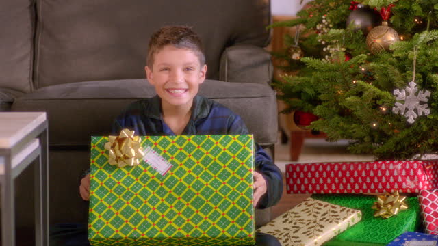Excited young boy shakes Christmas present for camera