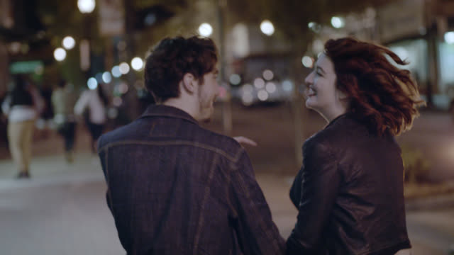 MS SLO MO. Excited young couple hold hands walking down city sidewalk at night.