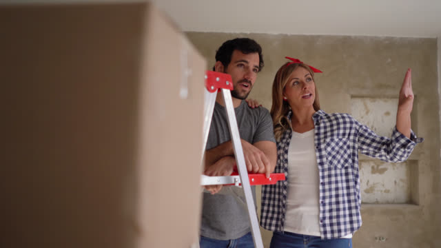 excited young couple planning their home renovation talking and pointing away very happy - renovation stock videos & royalty-free footage