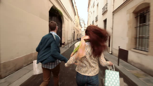 Excited young couple run down narrow Paris street with shopping bags.