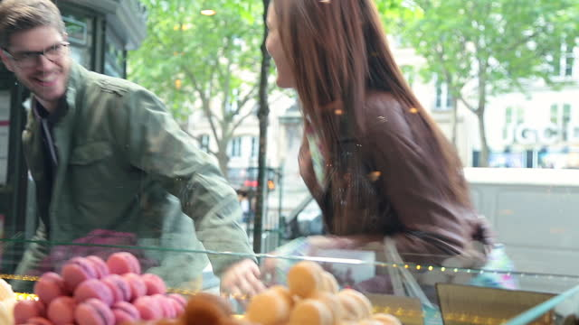 excited young couple stop to look at colorful macaroons in the window of a french bakery and point out the ones they want. - cream cake stock videos & royalty-free footage
