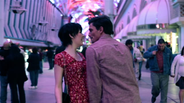 excited young couple take in the sights and sounds of fremont street in downtown las vegas - neon video stock e b–roll