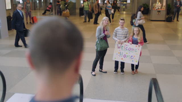 vídeos y material grabado en eventos de stock de excited young daughter, son and mother wait to greet father as he descends escalator at arrivals. - arrival