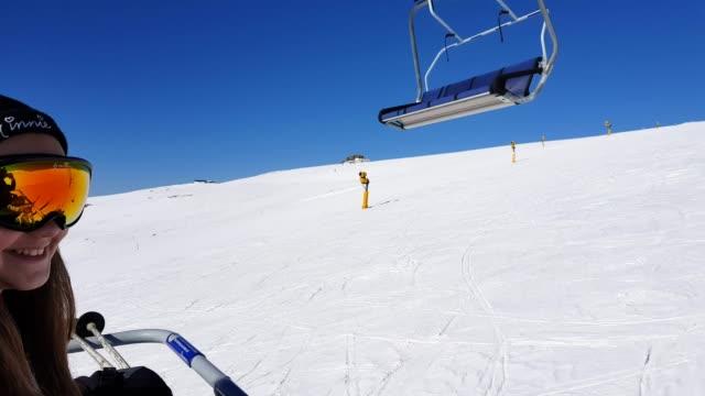 excited young girl riding the ski lift on a beautiful sunny day - inquadratura dalla sciovia video stock e b–roll
