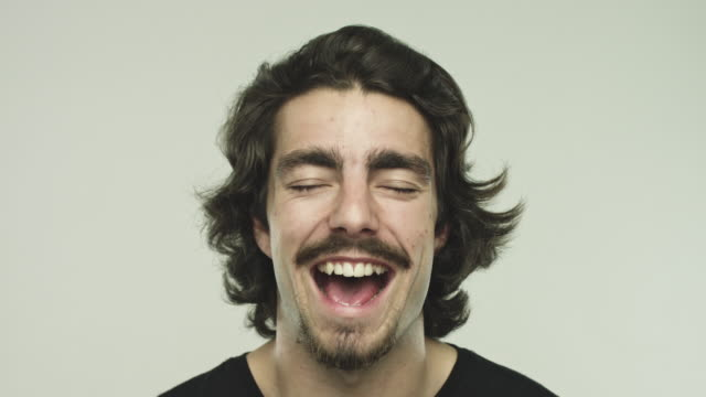 Excited young man laughing with eyes closed