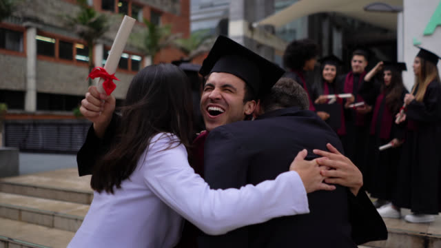 excited young man running towards parents hugging them after receiving his college diploma all smiling - diploma stock videos & royalty-free footage