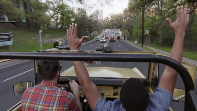 vídeos y material grabado en eventos de stock de excited young men clap and cheer in classic bronco approaching downtown austin, texas - pasear en coche sin destino