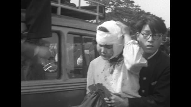 excited young people run past camera / men support a woman with a bloodied face and a young man supports a woman with a large head bandage - 病気点の映像素材/bロール