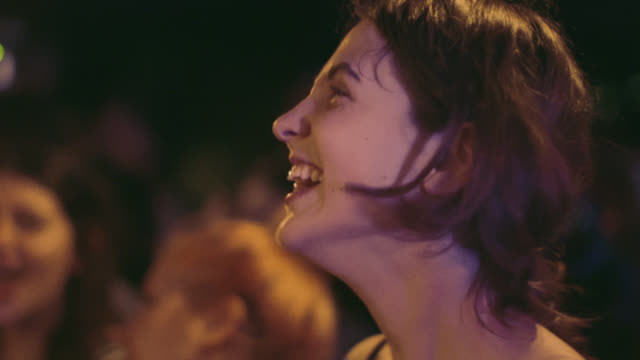 Excited young woman cheers for band at crowded rock show