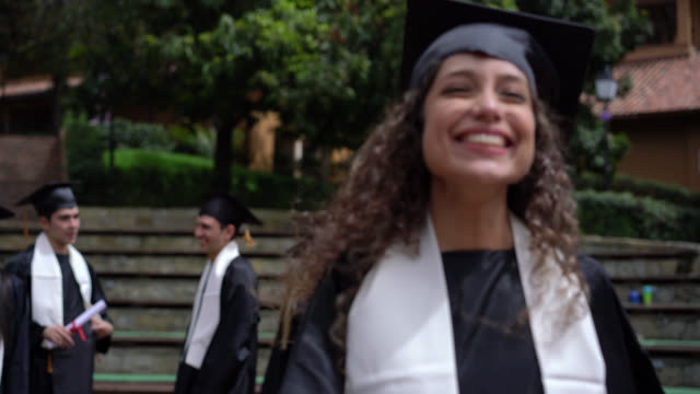excited young woman hugging to celebrate with her parents after graduating - graduation stock videos & royalty-free footage
