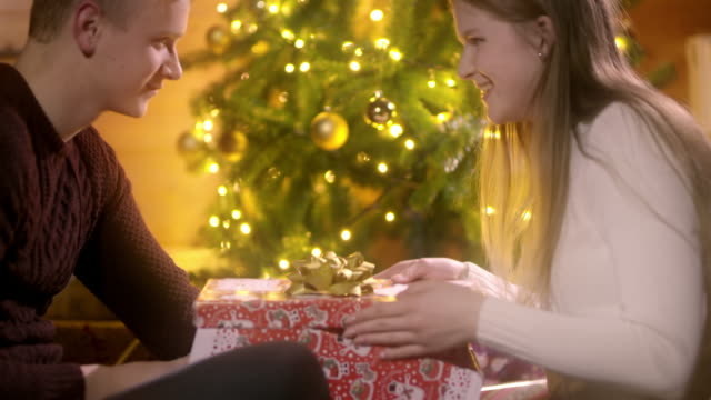 DS Excited young woman opening her Christmas present