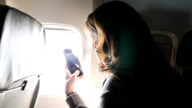 excited young woman snaps photos while on airplane - landing touching down stock videos & royalty-free footage