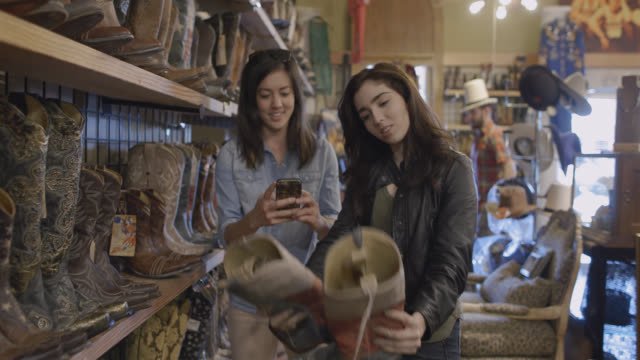 excited young women look at cowboy boots and take smartphone photo in western store - plug socket stock videos and b-roll footage