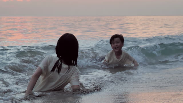 excitement joyful asian little boy and girl with fun along edge of sunset sea surf on sand beach.vacations - sister stock videos & royalty-free footage