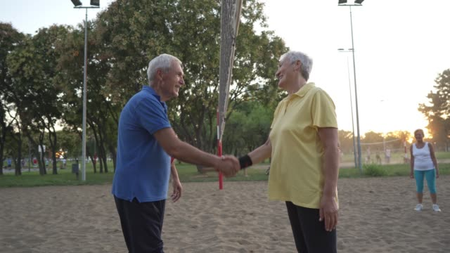 exctied senior man and woman handshaking after good volleyball game in the sand - sports period stock videos & royalty-free footage