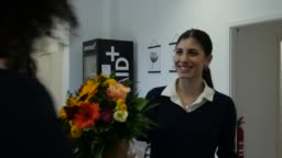 Executive admiring female colleague with bouquet