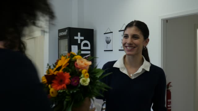 executive admiring female colleague with bouquet - bouquet stock videos & royalty-free footage