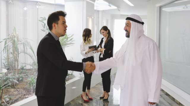 executive businessman shaking hands with a arab businessman - middle eastern culture stock videos and b-roll footage