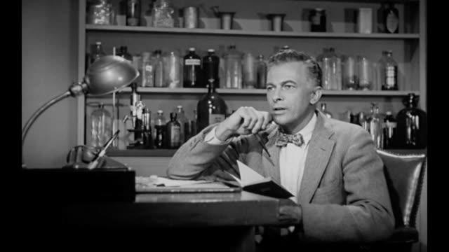 stockvideo's en b-roll-footage met 1959 executive discusses findings in scientist's notebook aloud to himself - 1959