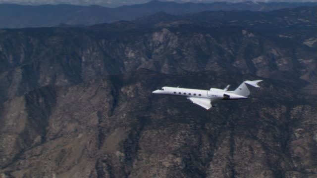executive jet over rugged terrain, left side - artbeats stock videos & royalty-free footage