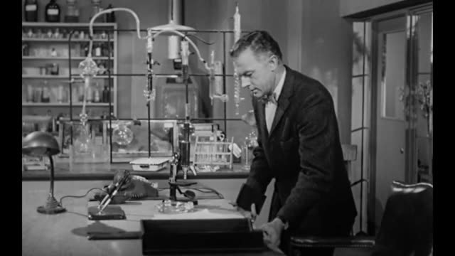 1959 executive sneaks into laboratory to investigate but hides when company owner (susan cabot) comes in - nosy stock videos and b-roll footage