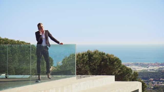 vídeos de stock, filmes e b-roll de executivo, falando no telefone na varanda contra o céu - full length