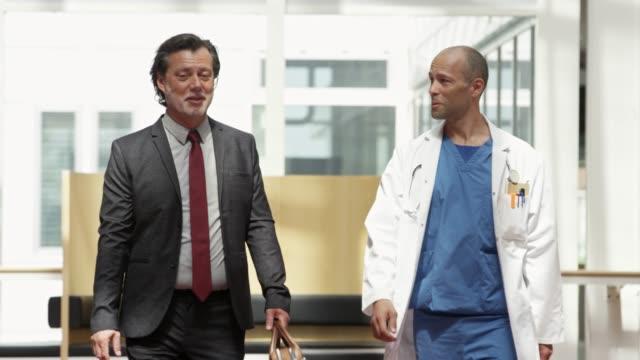 vídeos y material grabado en eventos de stock de ejecutivo hablando con el médico mientras camina juntos - oficio de ventas