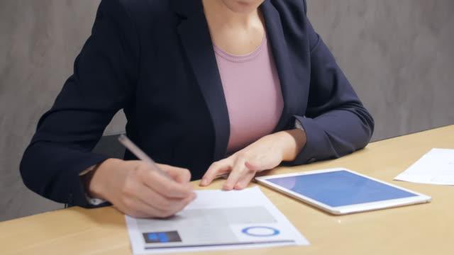 Executive mit Tablette während der Analyse der Dokumente