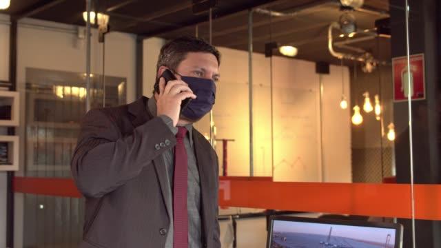 vídeos de stock, filmes e b-roll de executivo usando máscara no trabalho - só um homem